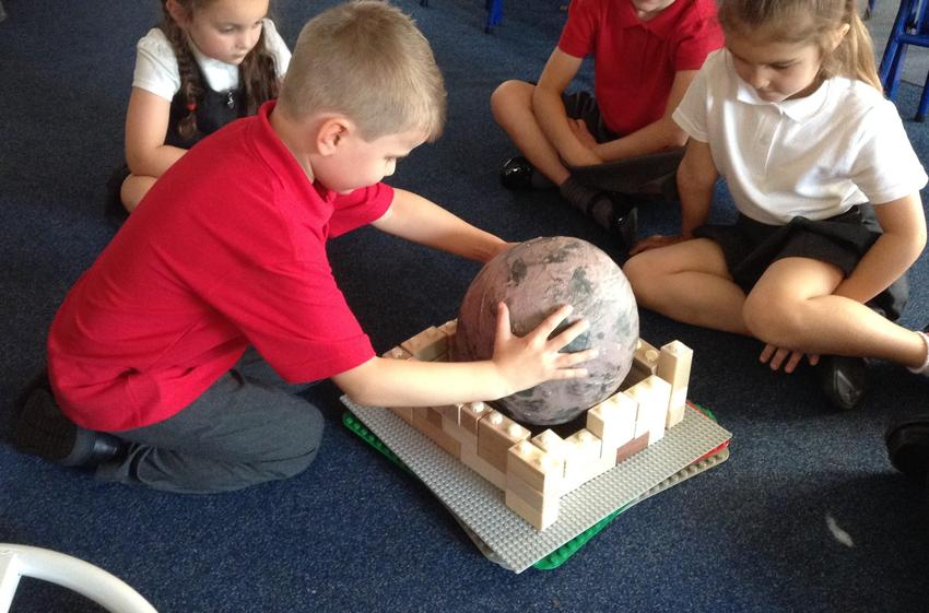 Building a nest out of wooden blocks.