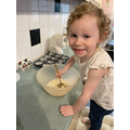 Gracie is following simple instructions while baking.