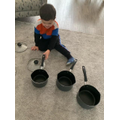 Joshua is putting the pans in size order