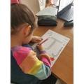 Isabel is using different colour pens to create a rainbow letter J