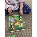 Sophie is moving jigsaw pieces around to fit!
