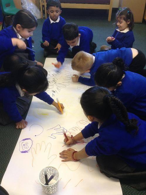Making a colourful shared picture in group time.