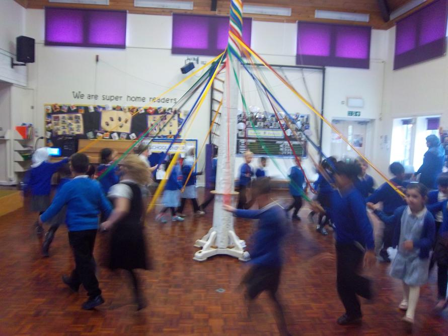 The children are getting really good moving around the maypole.