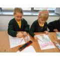 Ella and Scarlett making crayon and paint menorahs
