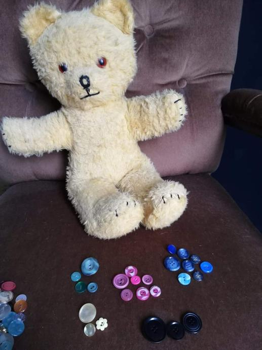 Little Ted separated the buttons into different coloured piles.