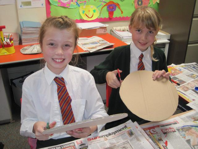 We cut out cardboard to make a round shield