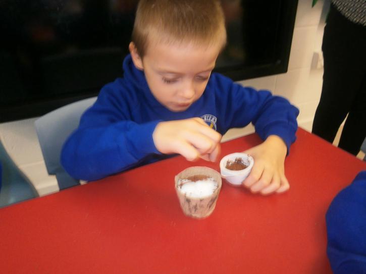 Makenzie using a pincer grip to add seeds