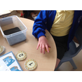 Poppie matching coins to the numerals.