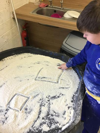 matthew uses his forefinger to make patterns in the flour.