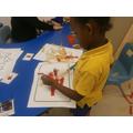 Hafsa independently using art materials