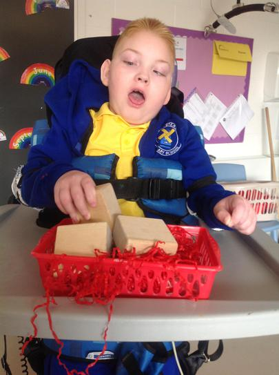 Kye picking up blocks to build a tower.