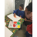 Zinet enjoying printing with fruit in a creative session