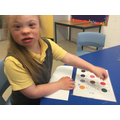 Grace using a communication board during a creative session