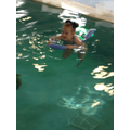Liliana using her noodle to practice her swimming