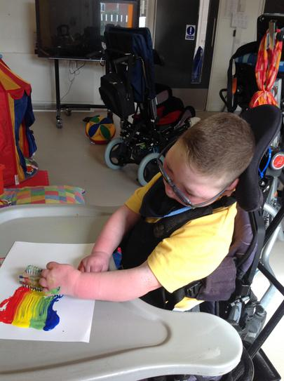 Joe making a rainbow with a nailbrush in paint.