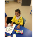Zinet using stamps to decorate her cup cake during a creative session