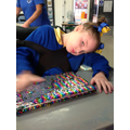 Louise making different marks on rainbow sequins