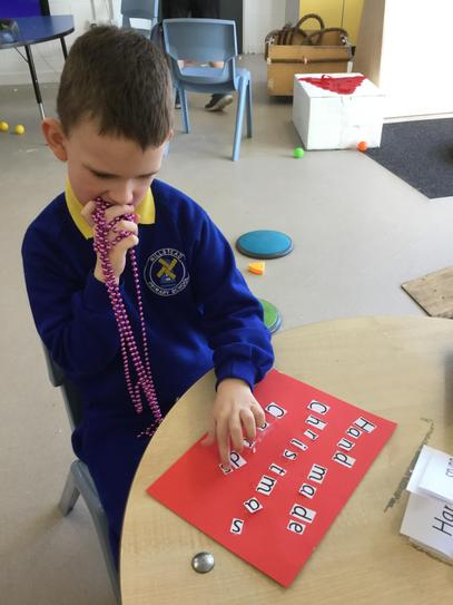 Using his phonic skills to write our sign.