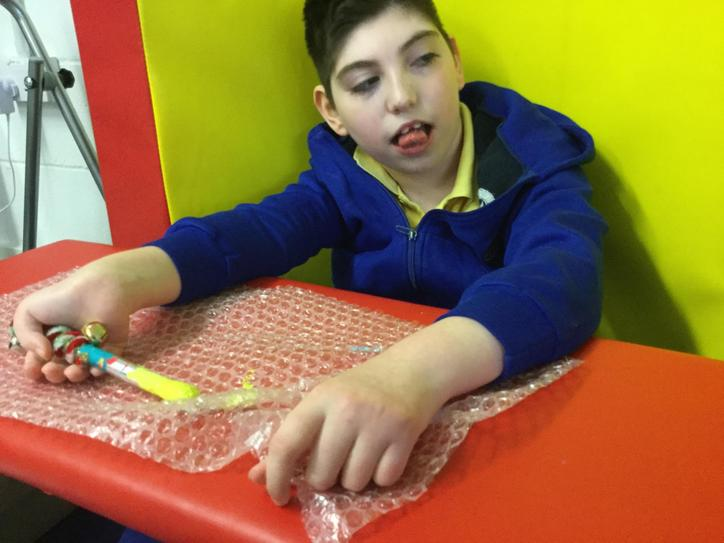 20/5 Jake sat on the floor with support at his back to do his art work