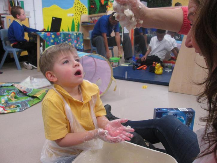 Connor anticipating adult sprinkling messy play