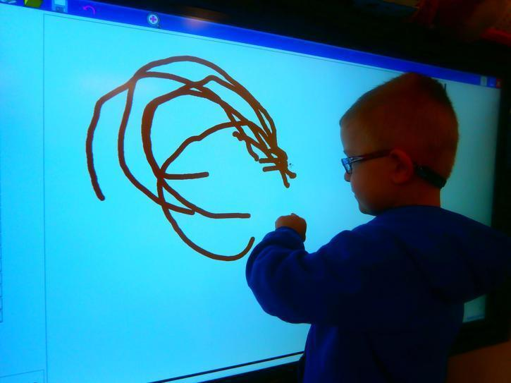 Ellis making marks on the interactive white board
