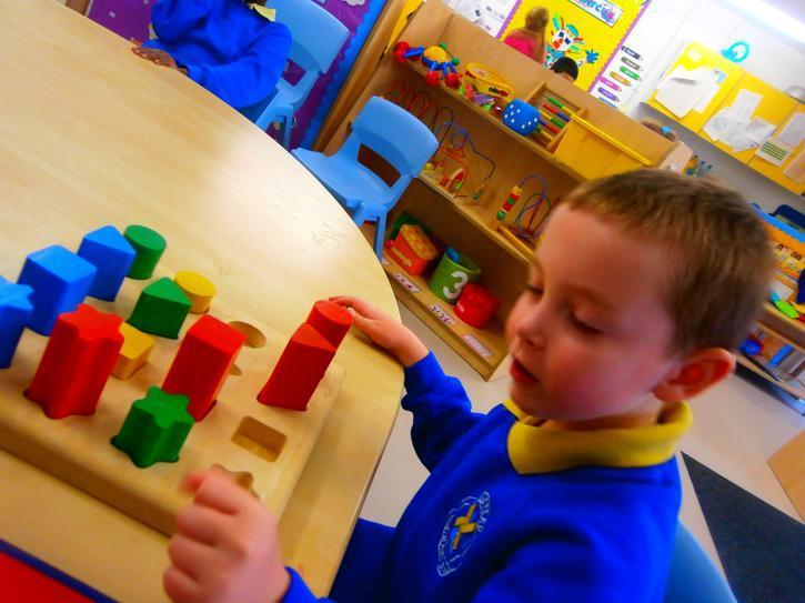 Charlie independently completing an inset puzzle