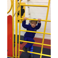 Elliot is climbing the climbing frame.