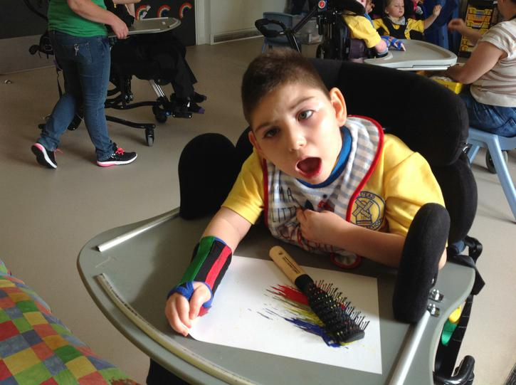 Jake making a rainbow using a hairbrush in paint.