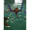 Grace using her noodle to practice her swimming
