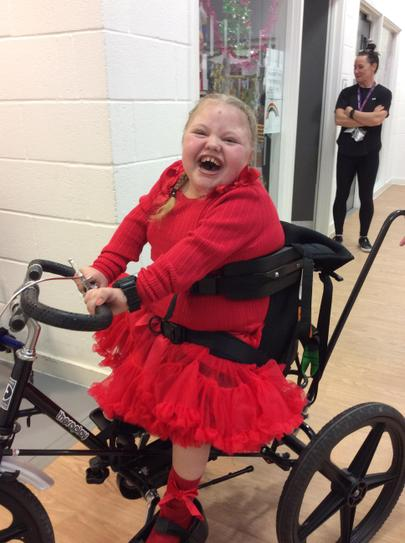16 /12 Lexi riding an adapted bike look at her smile.