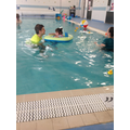 Emily moving independently in the pool.