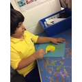 Muizz can paint independently fully engaged.