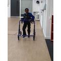 Josh using a Rifton walker to help him walk.