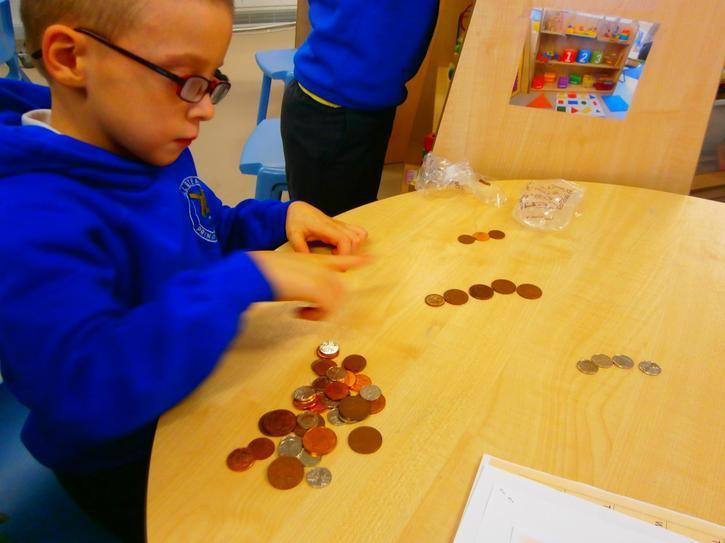 Makenzie independently sorting coins into 3 piles