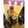 Connor copying an adult banging on the drum