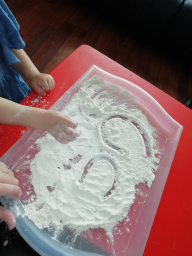 Isabelle writing letters in flour.