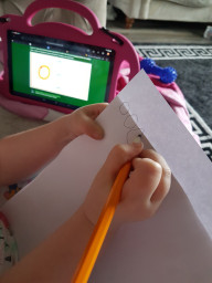 Kelsi writing 'o'.  Well done
