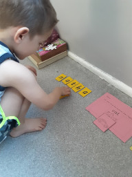 Nathan is using letter cards to spell his name.