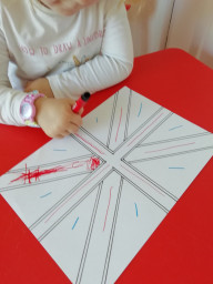 Isabelle is colouring a flag for VE Day.
