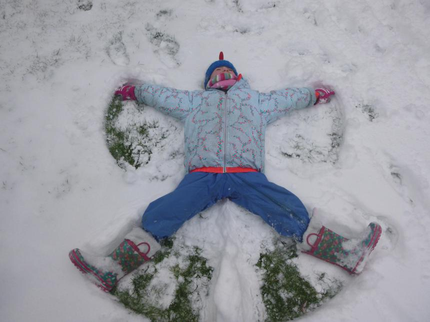 Trinity making snow angels,