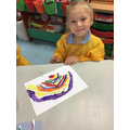Marcella painted a beautiful picture of a rainbow using cotton buds
