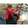 Playing with the cars in the outdoor area.