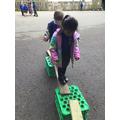 Khadija and Ronnie Jay balance well as they walk across the planks
