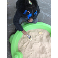 Looking for fossils in the sand. We used brushes to help see the footprints clearly.