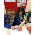 Supporting each other to use a compass and compare the sun, Earth and moon.