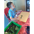 Joshua starting his car made from leaves and twigs