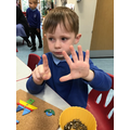 Sonny uses his fingers to represent numbers during play.