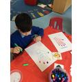 Eli drew patterns on his hand print.