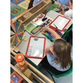 Zuzanna working on her addition using different resources.
