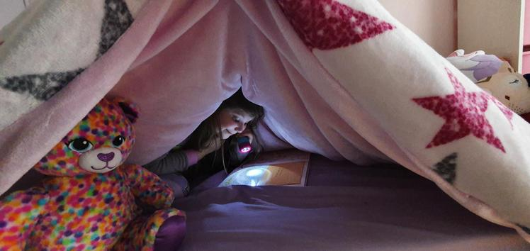 Sofia reading under her covers